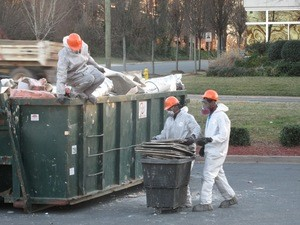 Water Damage Restoration Technicians Removing Debris To Street Dumpster